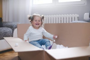 Little girl in moving box, moving to temporary housing