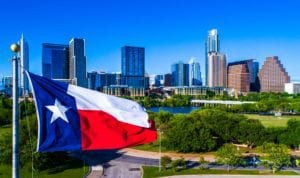 Texas Flag waving above Austin Skyline