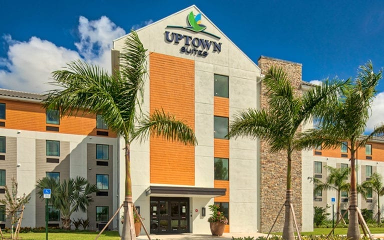 Exterior of Uptown Suites Extended Stay in Homestead, FL with two palm trees on the front and sunny sky