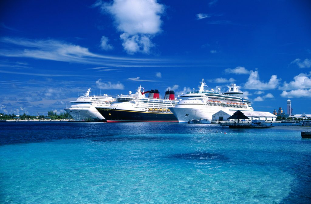 Cruise ships sitting in a bay of the Caribbean waiting to receive customers.
