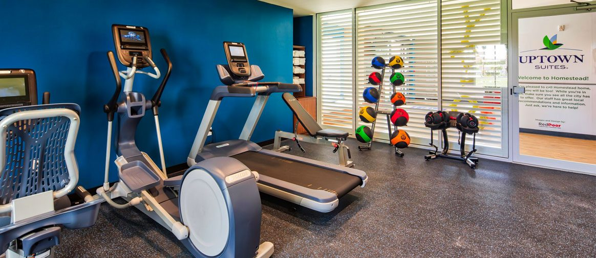 cardio equipment, dumbbells, and exercise balls visible in gym with blue walls