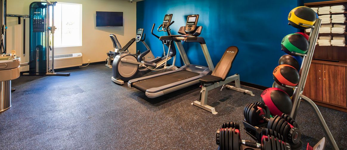 24/7 gym with adjustable dumbbells, exercise balls, cardio machines, and cable station