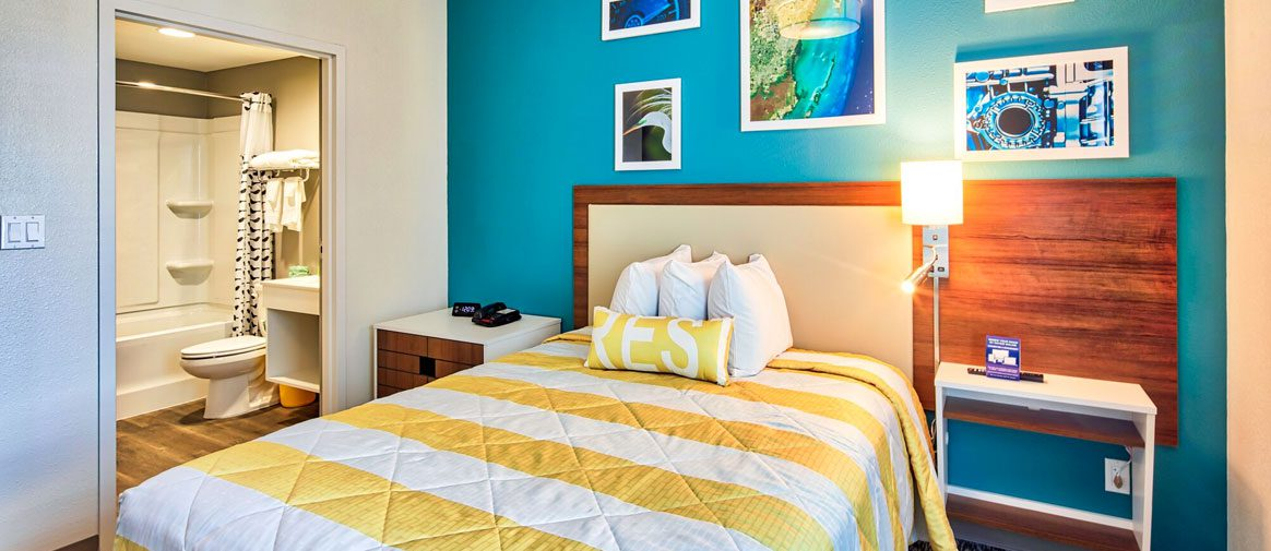 Well-lighted single guest room featuring a yellow and white striped bedspread is visible as well as the guest bathroom