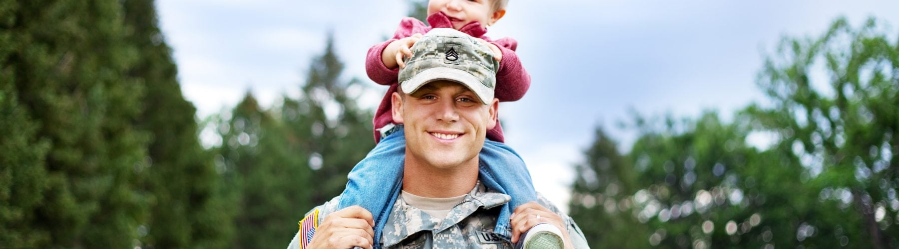 Dad in uniform giving his child a piggy-back ride